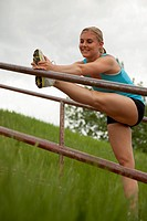 Young woman stretches her legs on a stair railing.