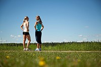 Two women joggers are standing by the side of the road and talking.