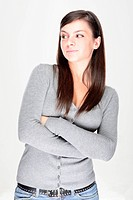 Close_up of a beautiful young woman on gray background, looking sideways.