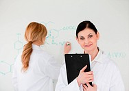 Scientist writting a formula helped by her assistant in a lab