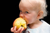 little girl bitting apple, closeup