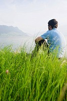 Man sitting on grass at Lake Lucerne, Switzerland, Europe