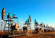 many working oil pumps in row under blue sky