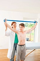 Physiotherapist working with a teenage boy with a Theraband