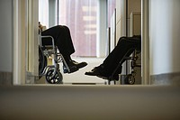 Low section view of two business executives sitting in wheelchairs