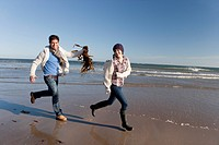 Man holding seaweed and chasing woman on sunny beach