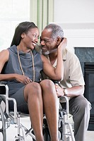 Middle_aged man romancing with a middle_aged woman sitting in a wheelchair and smiling