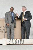 Two businessmen leaning against a cardboard box and smiling
