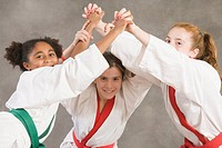 Portrait of three girls practicing karate