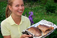 Young smiling woman holds fried fish