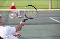 Side profile of a senior man sitting in a wheelchair and playing tennis