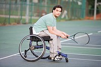 Mid adult man sitting in a wheelchair and holding a tennis racket in a tennis court