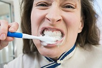 Portrait of a mid adult woman brushing her teeth