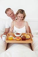 Couple having breakfast in bed