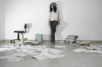 Unhappy woman standing against the wall looking at paperwork strewn on the floor.