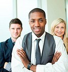 Afro_American businessman with his colleagues in folded arms smiling at the camera