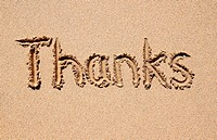 Thanks, written on a sandy beach.