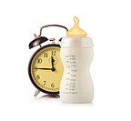Alarm clock and baby feeding bottle with milk isolated on white background