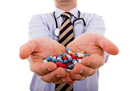 businessman holding a lot of pills in his hands selective focus