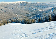 winter calm mountain landscape with ski tracks view from Bukovel ski resort Ukraine to Svydovets ridge
