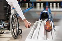 Low section view of a disabled man playing ten pin bowling