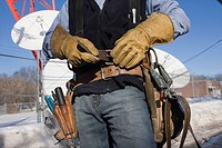 Cable lineman fastening his tool belt
