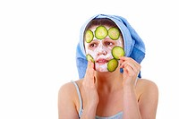 A young woman with a towel on her head, making a face mask with cucumber slices..