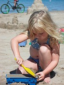 A young girl builds a sand castle at the beach.