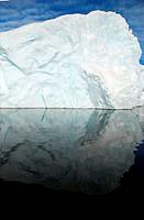 iceberg perfectly reflected in the dark ocean