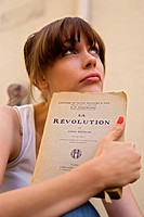 Young woman holding a book with the title La Revolution