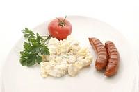 Kartoffelsalat mit zwei Bratwuerstchen, einer Tomate auf einem weissen Teller