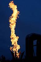 burning torch against industrial dusk background