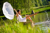 Happy romantic woman sitting by lake splashing water, holding parasol, wearing white dress