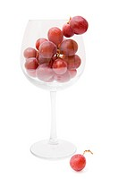 red grapes in a wine glass on a white background
