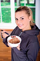 a young woman eating muesli in the kitchen