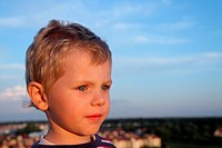Three years old boy over blue sky. Small town in a background