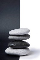 Black and white pebbles arranged in a stack with nice balance and a split black and white background