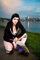 A beautiful caucasian skater teen girl outdoor during the sunset
