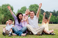 Happy family of five having fun by raising hands on the green land over natural background