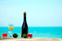 Bottle and glass of wine on the beach