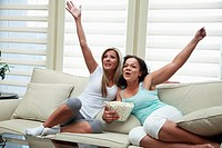 Two women cheer while watching a movie together on the couch.