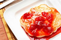 A closeup of pancake with strawberry syrup