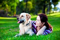 Young woman and golden retriever lying in the grass