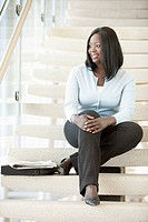A smiling businesswoman is sitting on a staircase with her hands folded on her knee.