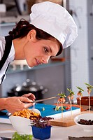 Female chef putting the finishing touch to a small amuse