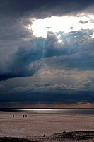 Cloudscape and walking people on the beach