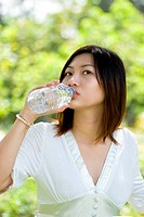 Woman drinking mineral water at the park