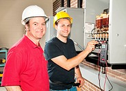 Apprentice electrician and his instructor reading the voltage on a power distribution center.