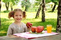 little girl with apple and juice in park