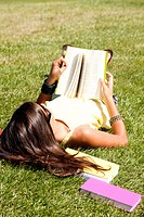little girl relaxing at the top of the field reading a book